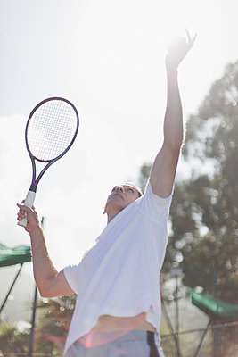 Older man serving tennis ball - p42916612f by Hybrid Images