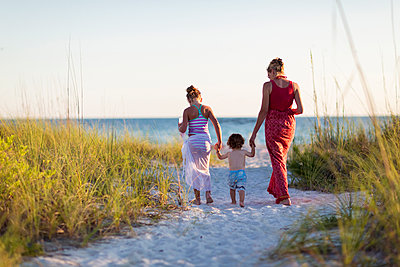 Caucasian mother and children walking on beach - p555m1411354 by Marc Romanelli