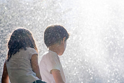 Children surrounded by spray from waterfall - p624m1180494 by Frederic Cirou