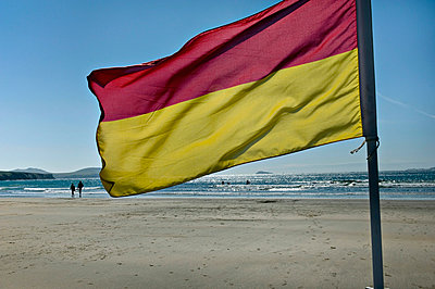 A flag flying on the beach of Whitesands Bay; Pembrokeshire, Wales - p644m728782 by Chris Parker