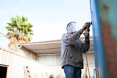 Welder using power tool on shipping container - p924m1422755 by Raphye Alexius