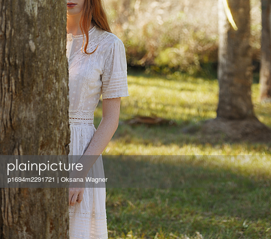 Unrecognizable red-haired young woman standing behind the tree in a sunny forest   - p1694m2291721 by Oksana Wagner