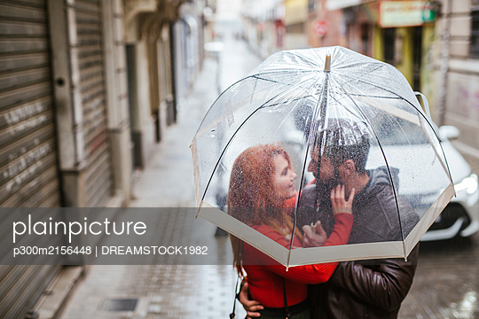 Couple in love under transparent umbrella in the city - p300m2156448 by DREAMSTOCK1982