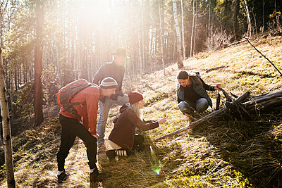 Friends hiking in sunny woods - p1192m2094236 by Hero Images