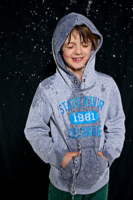 Boy wearing hooded shirt gets wet - p1355m1208920 by Tomasrodriguez