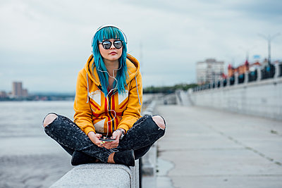 Young woman with dyed blue hair sitting on a wall listening music with headphones and smartphone - p300m2062873 by Vasily Pindyurin
