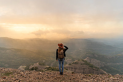 Woman with backback, standing on mountain, looking at view - p300m2078741 von VITTA GALLERY