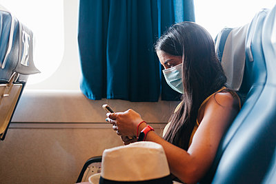 Woman wearing mask using smart phone while sitting on seat in cruise ship - p300m2220802 by Ezequiel Giménez