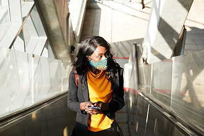 Thoughtful female entrepreneur with mobile phone on escalator during COVID-19 - p300m2241579 by Pete Muller