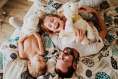 Laughing father and daughter playing while lying on bed with son at home - p300m2266273 by Gala Martínez López