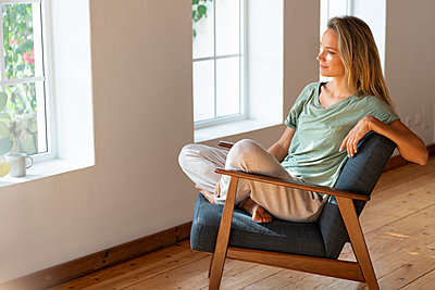 Relaxed woman day dreaming while sitting cross-legged on chair at home - p300m2277488 by Steve Brookland