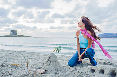 Caucasian woman building sandcastle on beach - p555m1411202 by Alberto Guglielmi