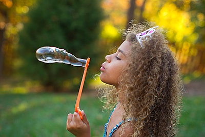 Mixed race girl blowing bubbles outdoors - p555m1419857 by Jeff Greenough
