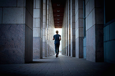 Young man running along urban sidewalk - p924m896123f by heshphoto