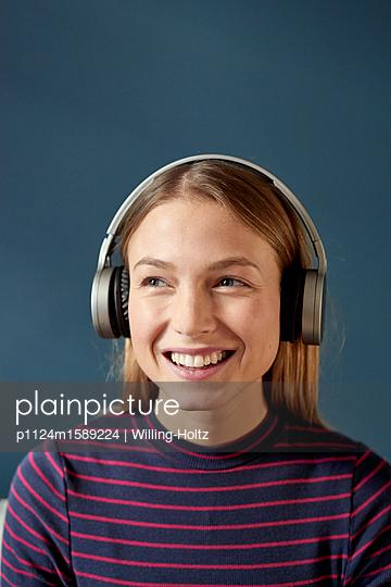 Junge Frau hört Musik über Kopfhörer - p1124m1589224 von Willing-Holtz