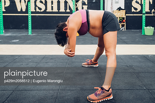 Pregnant woman bending forward at workout - p429m2058512 by Eugenio Marongiu