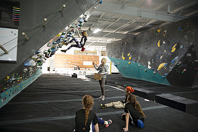Female instructor teaching girl rock climber students at climbing wall in climbing gym - p1192m1560050 by Hero Images