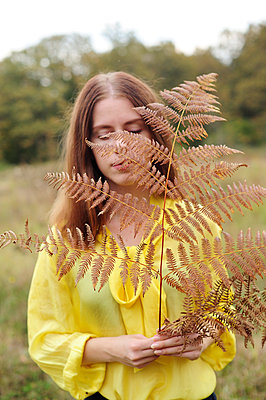 Teenage girl in yellow blouse holding fern in hand - p1412m2128859 by Svetlana Shemeleva