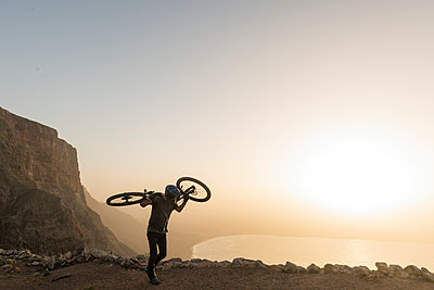 Spain, Lanzarote, mountainbiker on a trip at the coast at sunset carrying his bike - p300m2102706 by Hernandez and Sorokina