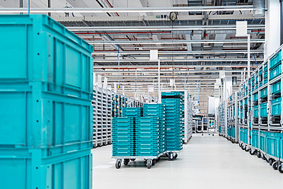 Turquoise colored containers inside modern factory warehouse, Stuttgart, Germany - p300m2131802 by Daniel Ingold