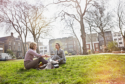 Two businesswomen sitting on grass in park - p429m803581f by Liam Norris