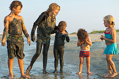 Caucasian brothers and sisters covered in mud playing on beach - p555m1522778 by Marc Romanelli