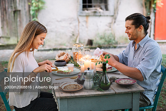 Couple having a romantic candelight meal next to a cottage - p300m2068816 by Alberto Bogo
