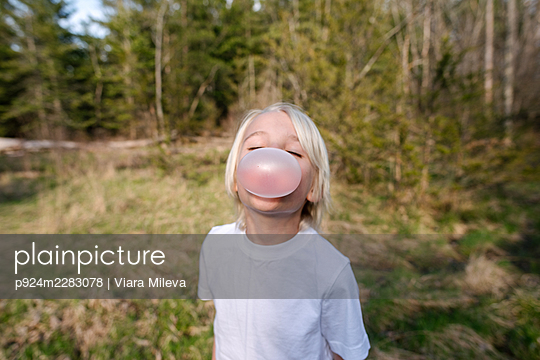 Canada, Ontario, Kingston, Portrait of boy blowing bubble gum in forest - p924m2283078 by Viara Mileva