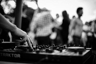 DJ playing music, in background group dancing - p1118m2143017 by Tarik Yaici