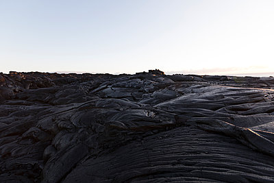 Volcanic rocks at beach against clear sky - p1166m1414572 by Cavan Images