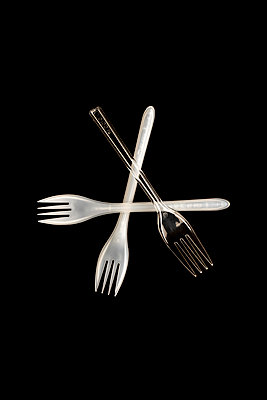 Three disposable plastic white and transparent forks on a black background - p1302m2044574 by Richard Nixon