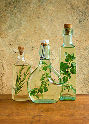 Olive oil bottles with mint, rosemary and oregano leaves - p1427m1517174 by Tetra Images