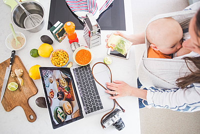 High angle view of female influencer food blogging while breastfeeding baby girl in kitchen - p426m2116966 by Maskot