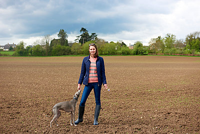 Mid adult woman and whippet dog in field, portrait - p429m2004471 by J J D