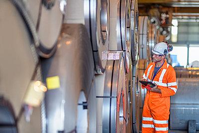 Worker using digital tablet by rows of sheet steel in storage at port - p429m2019461 by Monty Rakusen