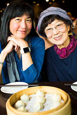 Older Japanese mother and daughter smiling in restaurant - p555m1302169 by Jed Share/Kaoru Share