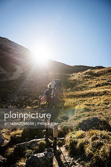 Junger Mann wandert Bergauf  - p1142m2056559 von Runar Lind