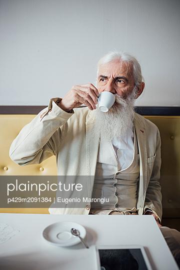 Senior businessman drinking coffee in cafe - p429m2091384 by Eugenio Marongiu