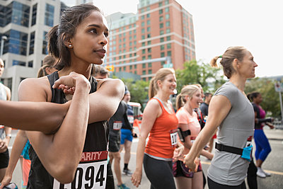 Focused female runner stretching arm on urban street - p1192m1490339 by Hero Images