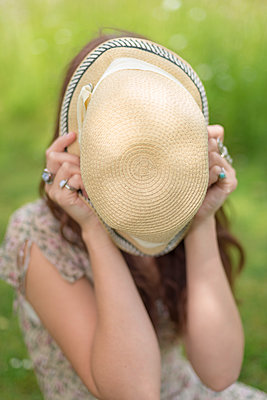 Young woman sitting on grass hiding her face behind a summer hat - p1433m1585125 by Wolf Kettler