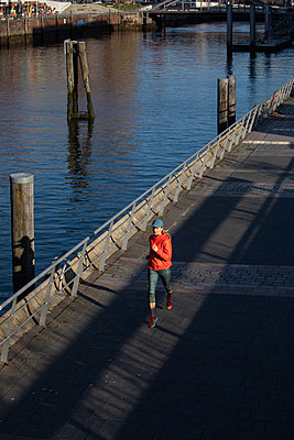Woman jogging in Hamburg - p1678m2262307 by vey Fotoproduction