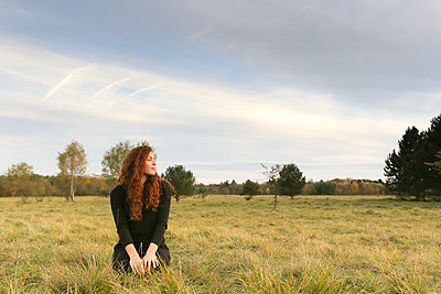 Redheaded young woman crouching on a meadow in autumn - p300m2059932 by Christina Falkenberg