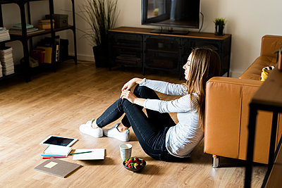 Relaxed young woman sitting on the floor at home having a break - p300m2119911 by Giorgio Fochesato