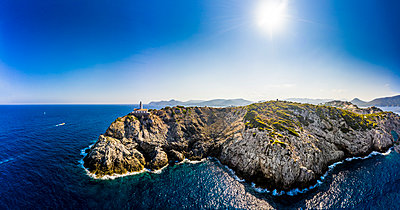 Spain, Mallorca, Cala Ratjada, Helicopter view of sun shining over coastal cliffs and Far de Capdepera lighthouse in summer - p300m2197326 by Martin Moxter