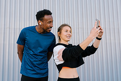 Female athlete with man taking selfie through mobile phone while standing against wall - p300m2265772 by Ezequiel Giménez