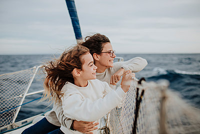 Mother and daughter looking at view while traveling on sailboat during vacation - p300m2276408 by Gala Martínez López