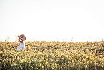 Girl with tousled hair running through agricultural field during sunset - p300m2276682 by Wilfried Feder