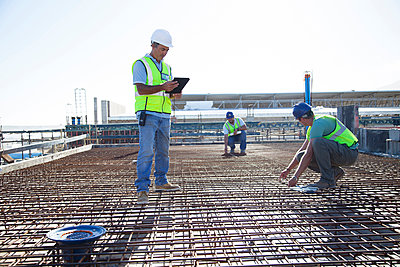 Construction workers arranging rebar at construction site - p555m1411753 by Resolution Productions