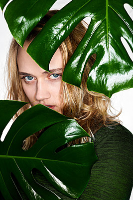 Young woman behind foliage plant - p890m2231054 by Mielek