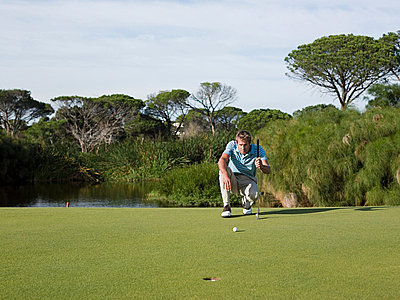 Man playing golf, on putting green - p9244377f by Image Source